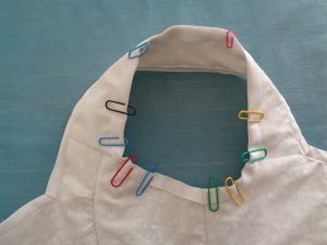 Use of paperclips to keep the bias tape in place around the stays' arm holes (© 2015 D.H. Morris)